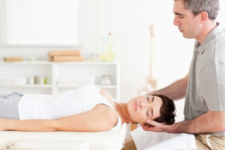 strength therapy: Chiropractor stretching a charming woman in a room Stock Photo
