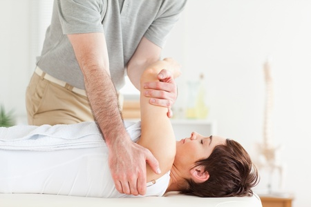 Man stretching a woman's arm in a room photo
