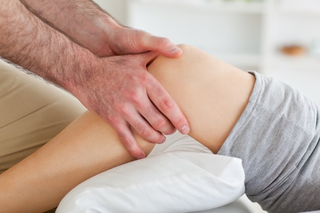 strength therapy: Man massaging a womans knee in a room