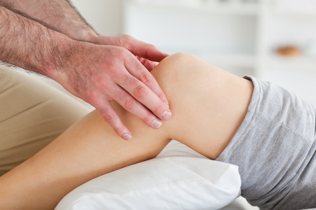 strength therapy: Man massaging a lying womans knee in a room