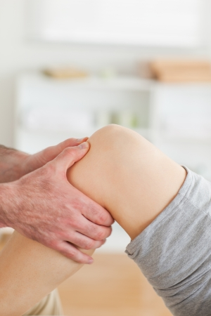 acupressure hands: Guy massaging a lying womans knee in a room