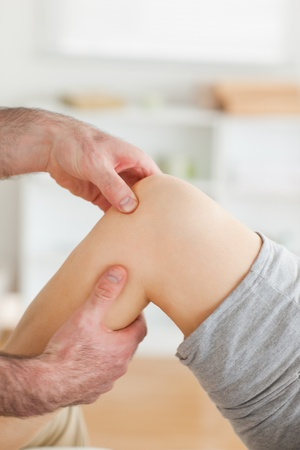 physical pressure: Guy massaging a knee in a room