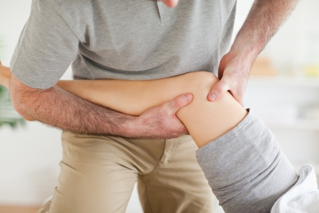 Chiropractor massaging a patients knee in a room photo