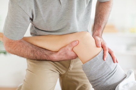 physical pressure: Chiropractor massaging a womans knee in a room