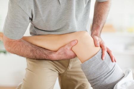 fysiotherapie: Chiropractor masseren van een vrouw knie in een kamer Stockfoto