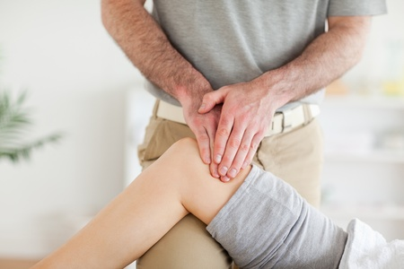 Chiropractor massaging a charming woman's knee in a room photo