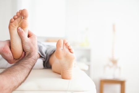 masseur: Male masseur doing a reflexology massage in a room