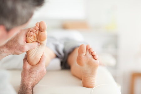 Lying Woman getting a reflexology massage by a man photo