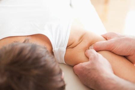 fysiotherapie: Man masseren van een vrouw schouder in een kamer