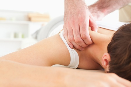 acupressure hands: Brunette Woman getting a neck-massage in a room