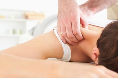 sports massage: Mujer Morena recibiendo un masaje de cuello en una habitaci�n