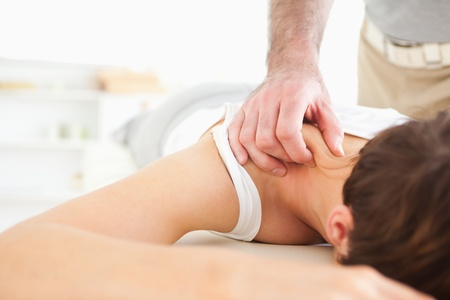 acupressure hands: Cute Woman getting a neck-massage in a room