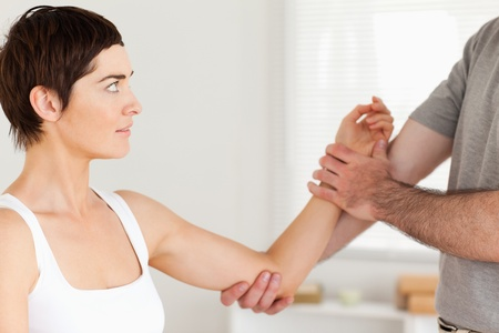 Chiropractor examining a woman's arm in a room photo