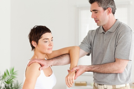 Chiropractor stretching a woman's arm in a room photo