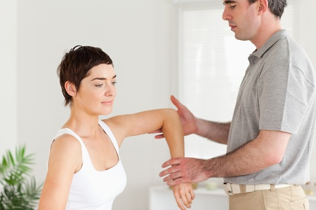 Chiropractor working on a womans arm in a room