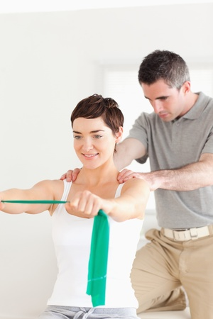 physical: Patient doing some exercises under supervision in a room Stock Photo