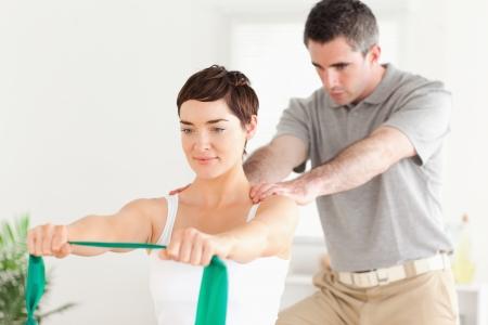 fisioterapia: Paciente lindo hacer algunos ejercicios bajo la supervisi�n de una habitaci�n