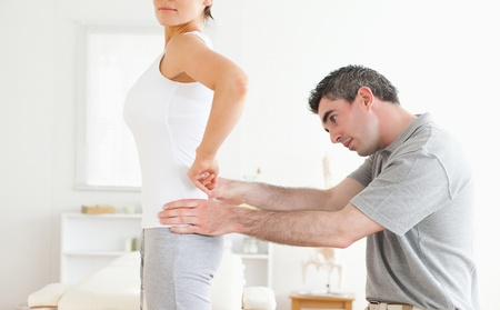 Chiropractor examining a cute woman's back in a room photo