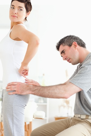 Chiropractor examining a brunette womans back in a room photo