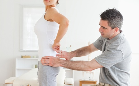 acupressure hands: Chiropractor examining a charming womans back in a room
