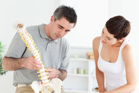 Chiropractor and patient looking at a model of a spine in a room photo