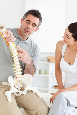 Chiropractor explaining the spine to a woman in a room photo