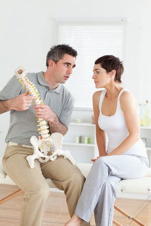 Woman listening to her chiropractor in a room Stock Photo - 11189794