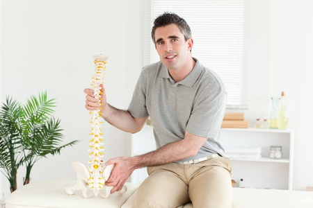 Chiropractor with the model of a spine in a room photo