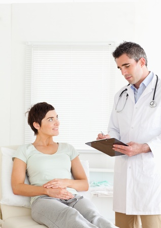 Woman lying down talking to a doctor in an office photo