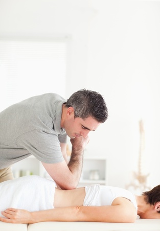 sports massage: Quiropr�ctico haciendo acupresi�n en la espalda de una mujer en una habitaci�n