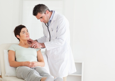 Male Doctor examining a patient in a room photo