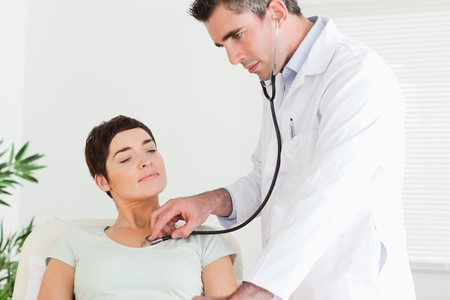 auscultate: Doctor examining a patient in a room