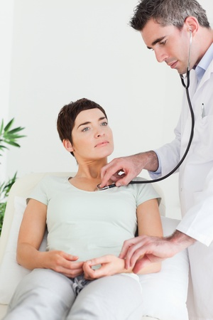 Doctor examining a female patient in a room photo