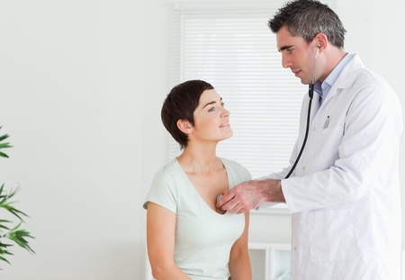 Doctor examining a woman in a room photo