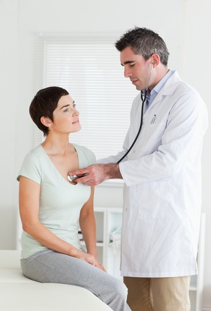 Doctor examining a brunette woman in a room photo