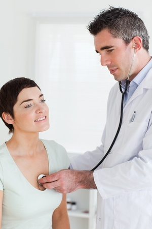 Cerca de un médico examina a una mujer morena en una habitación