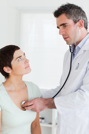 Doctor examining a charming woman in a room photo