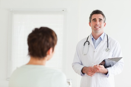 Smiling Doctor talking to a brunette woman in a room photo