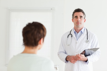 Serious Doctor talking to a brunette woman in a room photo
