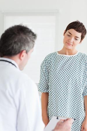 Mujer en bata de hospital hablando con su m�dico en una sala Foto de archivo - 11187293