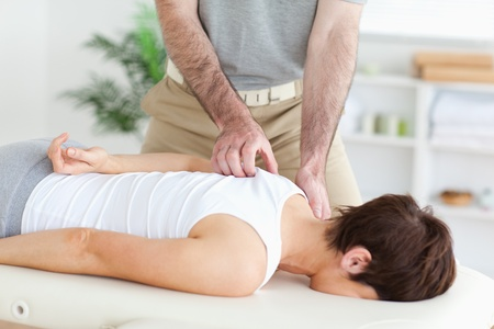 Masseur massaging a brunette woman's shoulder in a room photo