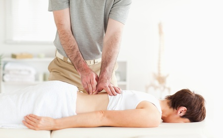 Brunette woman getting a back-massage in a room photo
