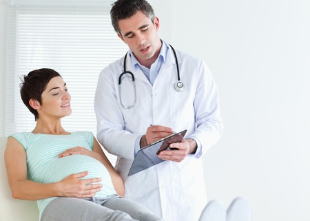 Pregnant woman lying down talking to her doctor in a room photo