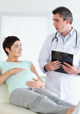 Doctor talking to a pregnant woman in a room photo