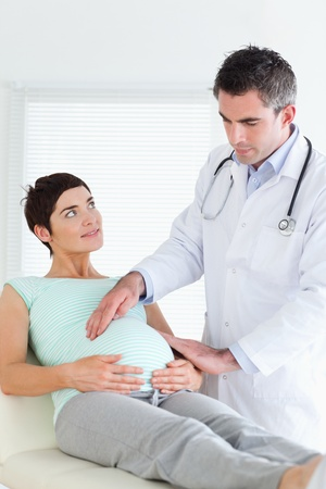 Doctor examining a pregnant woman's tummy in a room Stock Photo - 11191318