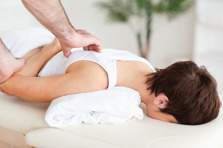 strength therapy: Gorgeous Woman getting a shoulder-massage in a room