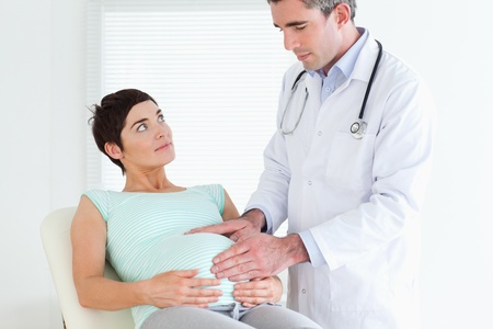 regnant: Doctor ausculating a pregnant womans belly in a room