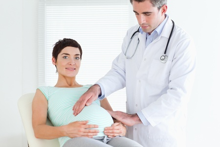 regnant: Male Doctor ausculating a pregnant womans tummy in a room