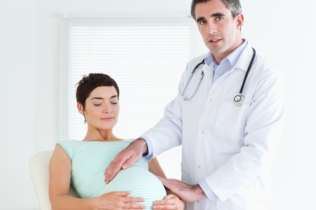 Male Doctor examining a pregnant woman's tummy in a room Stock Photo - 11213764