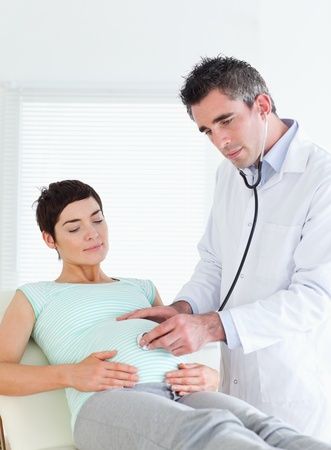 Doctor listening into the belly with a stethoscope in a room photo